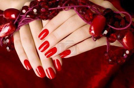 Photo pour Les mains de femme sur fond de velours rouge - image libre de droit