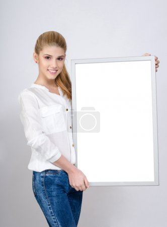 Young girl smiling and holding a white blank board.