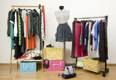Dressing closet with polka dots clothes arranged on hangers and an outfit on a mannequin.