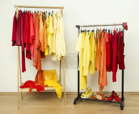 Shades of yellow, orange and red clothes hanging on a rack nicely arranged.