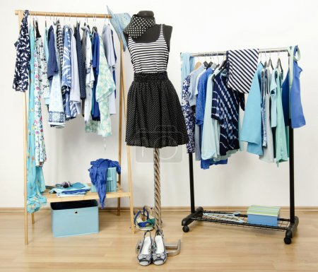 Photo for Dressing closet with blue clothes arranged on hangers. Dark blue stripes and polka dots outfit on a mannequin. - Royalty Free Image