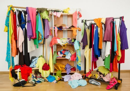 Photo for Messy clothes thrown on a shelf, on the ground and off the hangers and racks. - Royalty Free Image