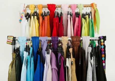 All colors clothes hanging on a rack nicely arrang...