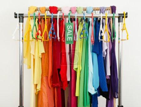 Foto de Señal de venta de ropa de verano en una parrilla de separación con verano coloridos trajes y accesorios. - Imagen libre de derechos