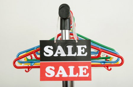 Close up on empty hangers and a big sale sign.