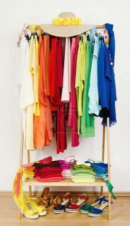 Photo for Dressing closet with color coordinated clothes on hangers, sandals and accessories. - Royalty Free Image