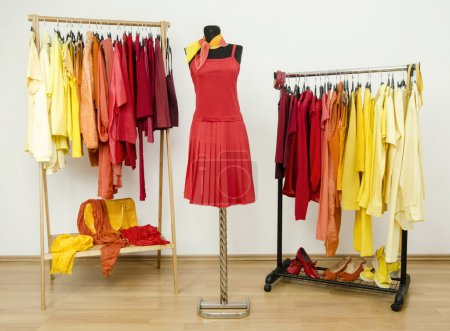 Photo for Dressing closet with bright color coordinated clothes on hangers, shoes and accessories. - Royalty Free Image