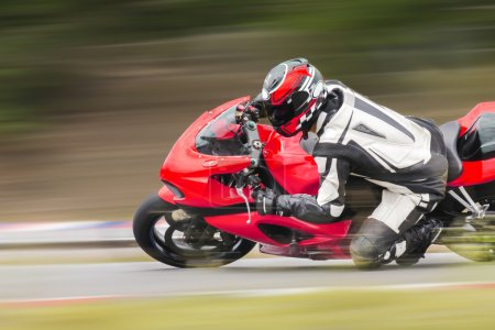 Racing bike rider leaning into a fast corner on track