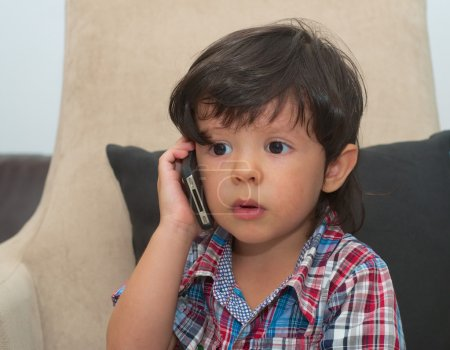 handsome smart kid talking by mobile phone