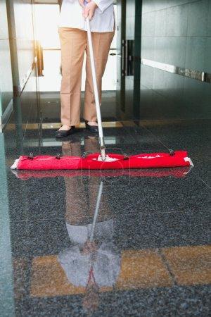 Photo pour Nettoyeur nettoie le sol dans un immeuble de bureaux - image libre de droit