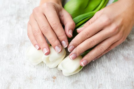 Photo for Female hands with french manicure and flowers - Royalty Free Image
