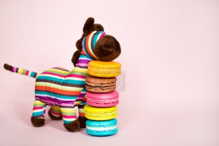 Photo for Traditional french colorful macarons inext to a colorful zebra - Royalty Free Image