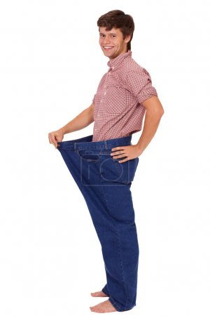Young slim happy handsome guy in jeans, isolated on white