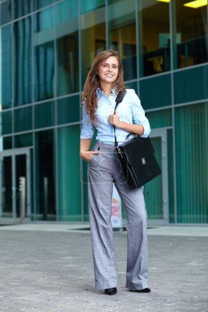 Foto de Retrato completo de una hermosa atractiva joven empresaria sonriente con maletín, fondo - Imagen libre de derechos