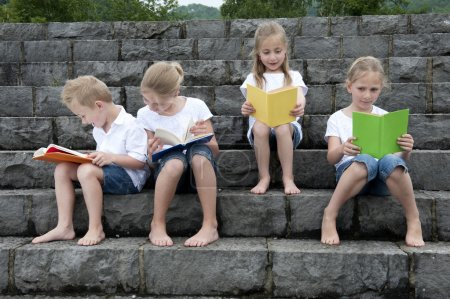 summer holidays: children with a book seated outdoors on stairs