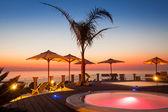 Letní čas: krásný pohled červené svítání v bazénu s palmami