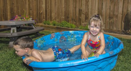 Young boy looking out of his paddling pool,young girl smiling at