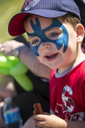 Young boy with blue face paint eating a hot dog