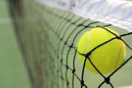 Photo pour Balle de tennis dans le net - image libre de droit