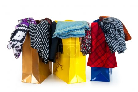 Color shopping bags with clothing isolated on white with reflection