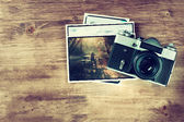 Top view of old vintage camera and pictures over wooden brown background.