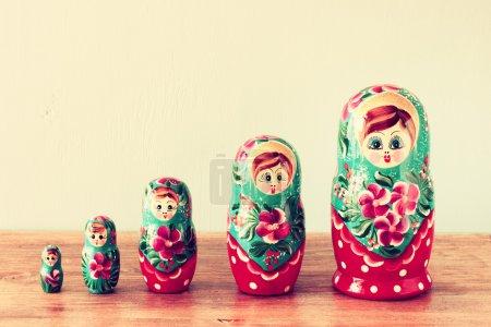 Photo pour Groupe de poupées matryoshka dans une rangée, avec un accent sélectif sur une poupée sur la table, sur un fond jaune pâle - image libre de droit