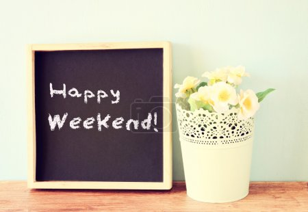Photo for Blackboard over wooden shelf with the phrase happy weekend - Royalty Free Image