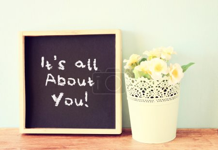 Photo for Blackboard with the phrase it's all about you written on it. over wooden shelf and flowers. - Royalty Free Image