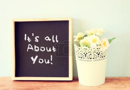 Photo pour Tableau noir avec les mots, c'est tout vous écrit à ce sujet. plus de fleurs et étagère en bois. - image libre de droit