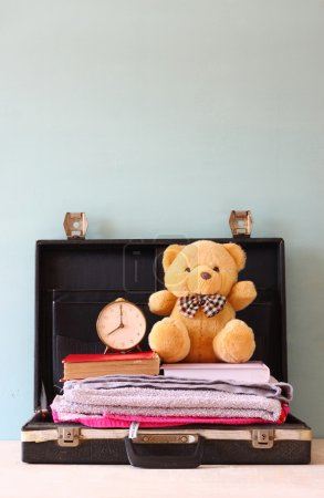 Photo for Open case with books towel teddy bear and vintage clock. vacation concept. - Royalty Free Image