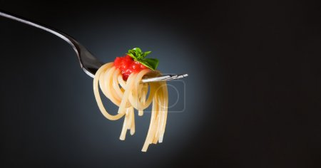 Photo for Spaghetti pasta with tomato and basil on fork. Fine Italian food. Space for text. Professional studio image - Royalty Free Image