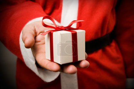 Photo for Santa Claus holding and offering a gift on his hand. - Royalty Free Image