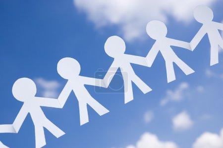 Photo pour Chaîne homme papier sur ciel bleu avec des nuages blancs. Symbole d'unité, de fraternité et de travail d'équipe . - image libre de droit