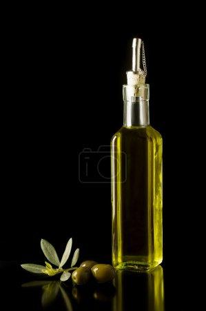 Photo pour Bouteille de fine huile d'olive extra-vierge italienne avec olives et quelques feuilles. - image libre de droit