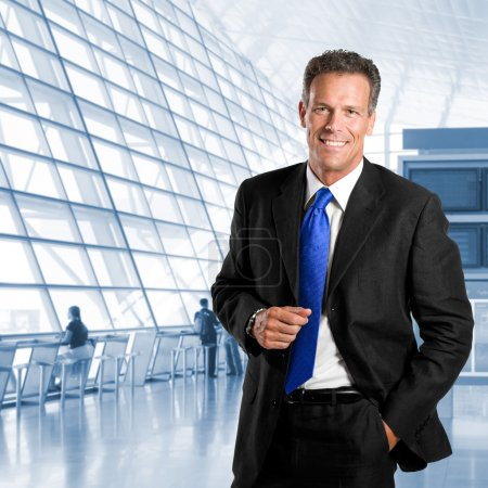Photo for Mature successful businessman smiling and looking at camera in a modern office building - Royalty Free Image