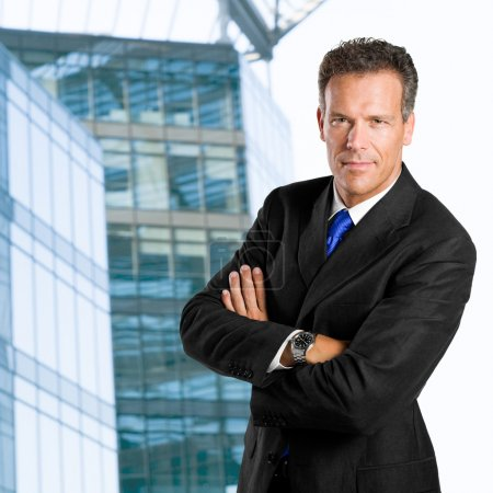 Photo for Mature businessman looking at camera with confidence against his office building - Royalty Free Image