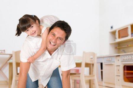 Photo pour Père souriant portant sur ses épaules sa petite fille à la maison - image libre de droit