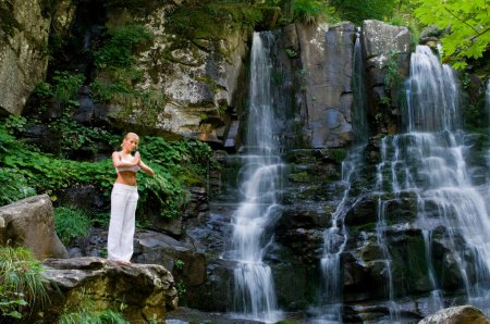 Photo for Beautiful young woman meditating while doing yoga in a wonderful forest near waterfall - Royalty Free Image