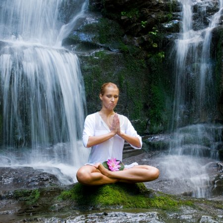 Young woman doing yoga near waterfalls