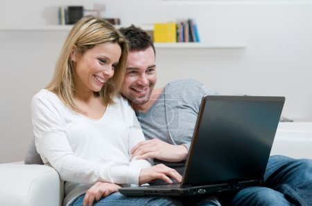Smiling young couple with laptop