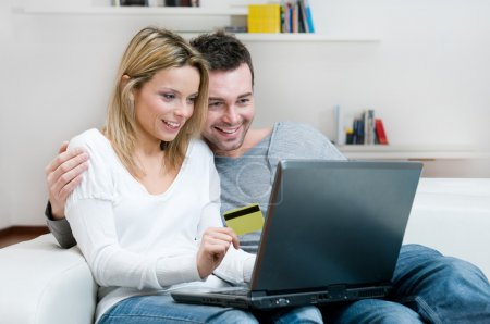 Photo for Young couple doing shopping in internet with credit card at home - Royalty Free Image