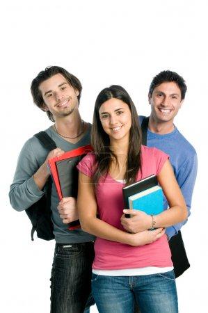 Photo pour Trois étudiants heureux permanent avec plaisir, tout en souriant et en regardant la caméra isolé sur fond blanc. - image libre de droit