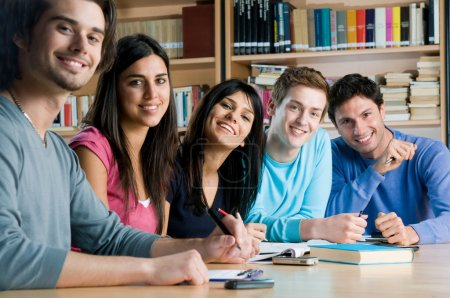 Photo for Happy group of young students studying together in a college library and looking at camera smiling - Royalty Free Image