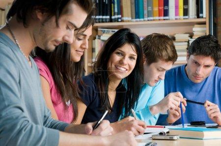 Photo pour Groupe de jeunes étudiants travaillant et étudiant dans une bibliothèque collégiale, fille souriante regardant la caméra . - image libre de droit
