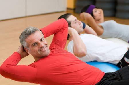 Photo for Healthy with mature instructor doing sit-ups at gym - Royalty Free Image