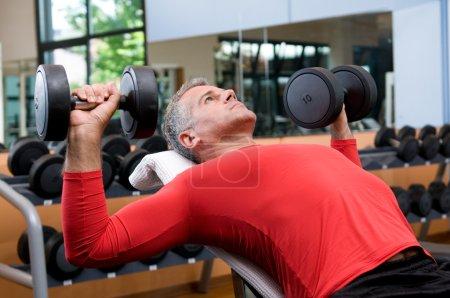 Photo pour Homme mature soulevant des haltères à la salle de fitness - image libre de droit