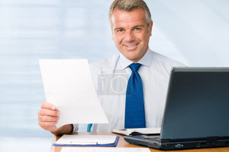 Photo for Mature positive businessman holding paperwork and looking at camera smiling - Royalty Free Image
