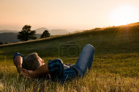 Photo for Mature man taking a break and relax in a meadow in the wonderful warm light of the sunset - Royalty Free Image