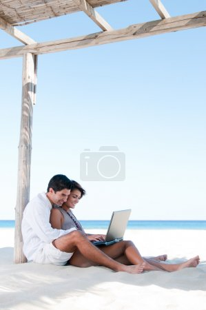 Photo for Beautiful young couple surfing the net together during summer vacation at tropical beach - Royalty Free Image