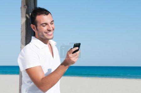 Photo pour Joyeux jeune homme regardant les nouvelles et la messagerie sur son téléphone intelligent à la plage - image libre de droit